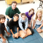 A group of teenage students learning Life Saving Skill